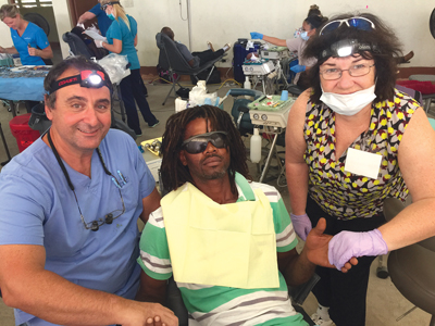 Dr. James Vassallo (retired, Mississauga) with a patient and Ann Bengert (TD Bank) assisting.