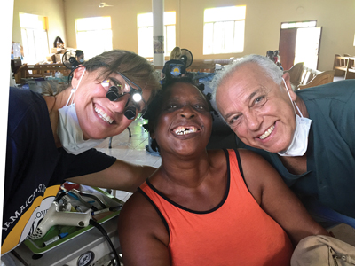 Dental Hygiene Instructor Sharon Crawford (left) and Dr. Samir Barsoum (Downsview) (right) with a happy patient at Savanna-la- Mar clinic.