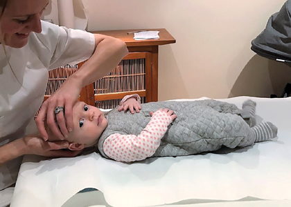 Osteopath working on infant with left torsion strain. Note the infant's relaxed posture.