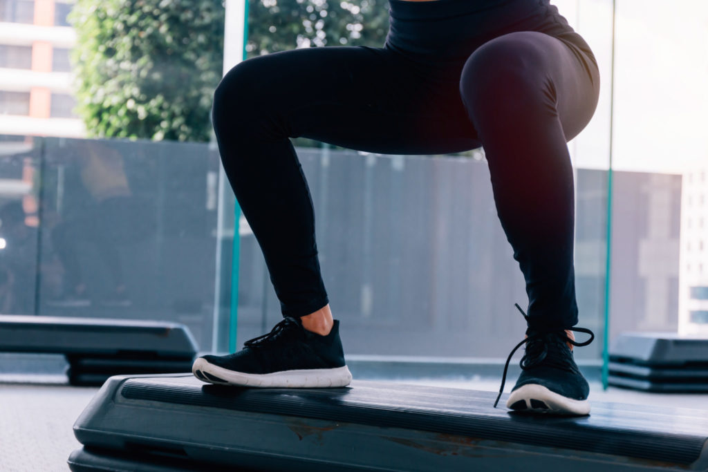 Bottom part of fitness woman in sportswear doing deep squat at gym- exercises